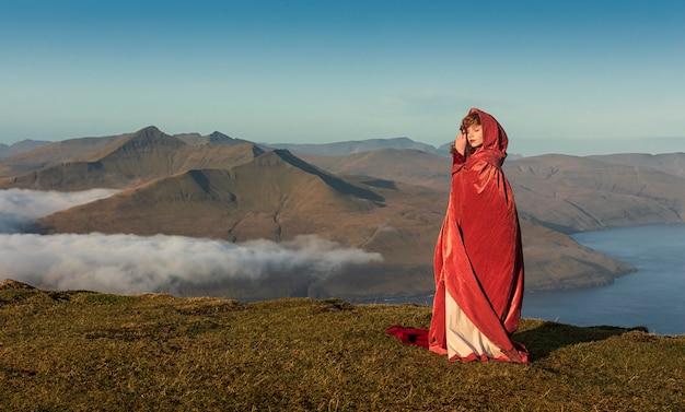 Uma jovem ruiva em roupas à moda antiga, com uma capa vermelha brilhante, fica no campo de grama nas terras altas. ilhas faroe, dinamarca Foto Premium