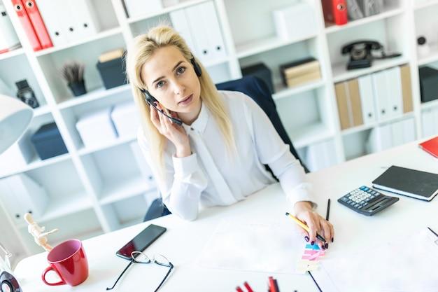 Uma jovem senta-se em fones de ouvido com um microfone na recepção no escritório e faz anotações no documento. Foto Premium