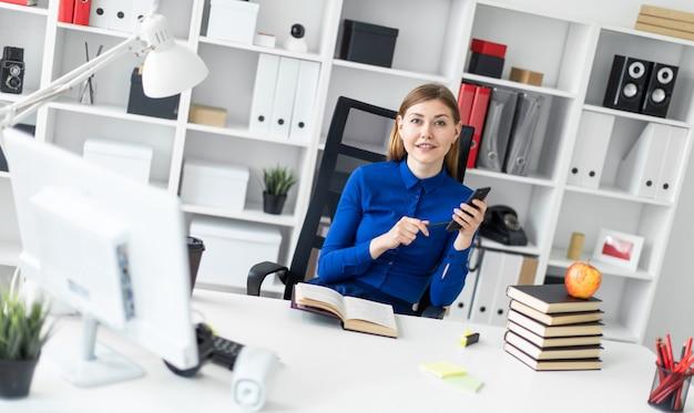 Uma jovem senta-se em uma mesa de computador e possui um telefone na mão. antes da menina encontra-se um livro aberto. Foto Premium