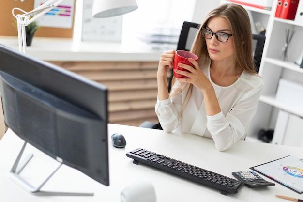 Uma jovem senta-se em uma mesa no escritório, detém um copo vermelho na mão e olha para o monitor. Foto Premium
