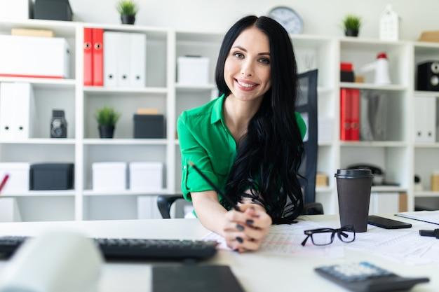 Uma jovem senta-se na mesa do escritório e detém um lápis nas mãos dela. Foto Premium