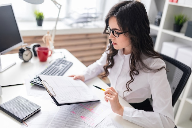 Uma jovem senta-se na mesa do escritório e verifica documentos. Foto Premium