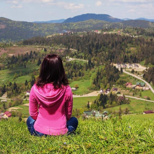Uma jovem senta-se no chão e olha para as montanhas. Foto Premium