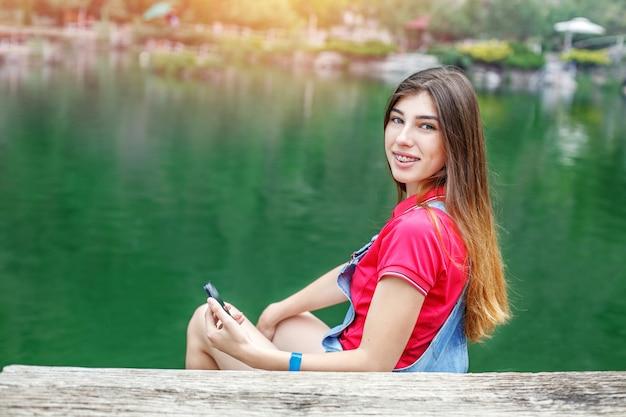 Uma jovem senta-se no lago e se comunica em redes sociais. Foto Premium