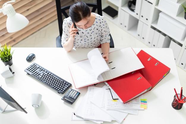 Uma jovem sentada no escritório, na mesa do computador, trabalhando com documentos e falando ao telefone. Foto Premium