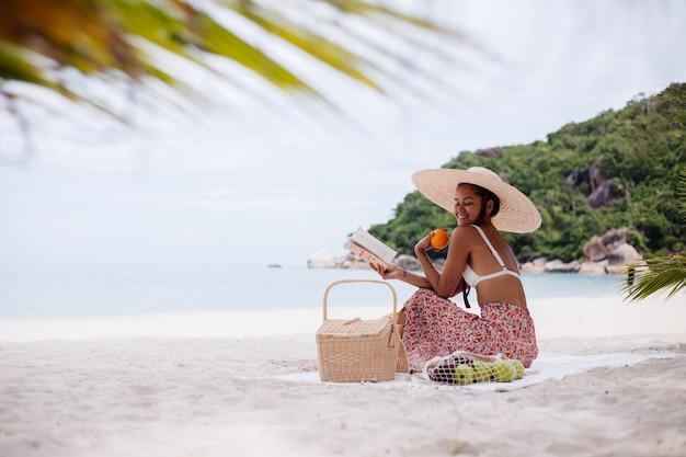 Uma jovem sentada no tapete da praia com um chapéu de palha e uma roupa de malha branca Foto gratuita