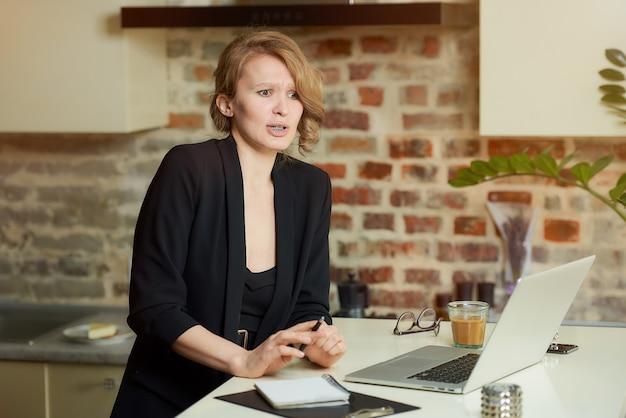 Uma jovem trabalha remotamente em um laptop na cozinha dela. uma chefe do sexo feminino se decepcionou com seus funcionários durante uma videoconferência em casa. Foto Premium