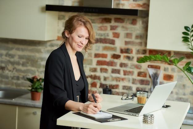 Uma jovem trabalha remotamente em um laptop na cozinha dela. uma chefe é feliz com seus funcionários durante uma videoconferência em casa. um professor escrevendo respostas dos alunos durante uma palestra on-line. Foto Premium