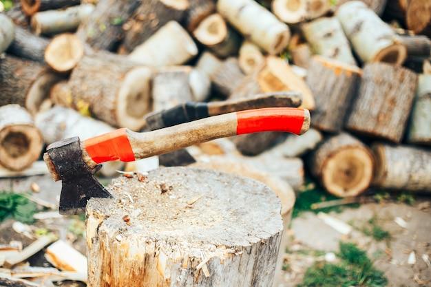 Uma lâmina afiada de um machado que se destaca em um calço de madeira. Foto Premium