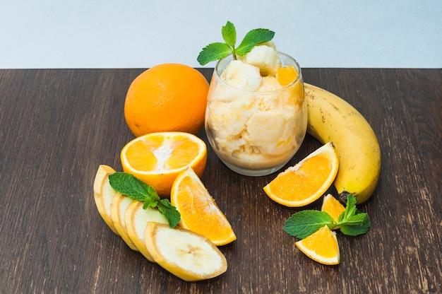 Uma laranja; sorvete de banana no plano de fundo texturizado de madeira contra o fundo azul Foto gratuita