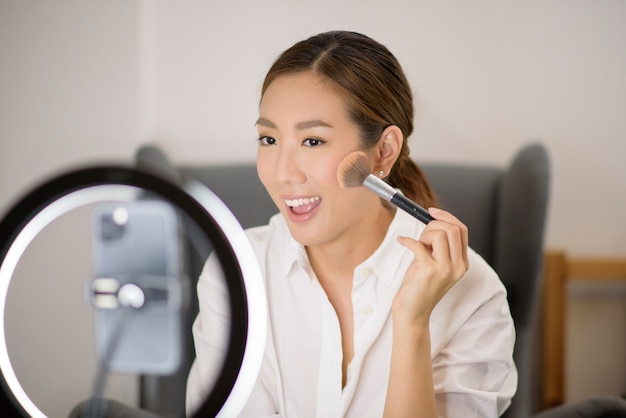 Uma linda blogueira de maquiagem asiática está transmitindo ao vivo como fazer maquiagem de rosto em casa Foto Premium