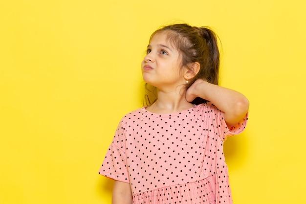 Uma linda criança de vestido rosa posando com uma expressão de descontentamento Foto gratuita