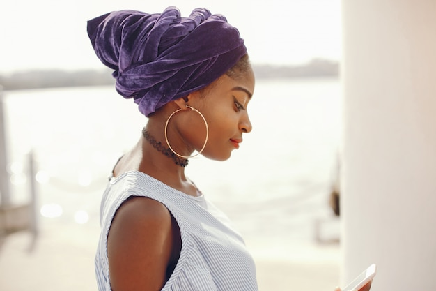 Uma linda e elegante garota de pele escura caminha em uma cidade de verão ensolarado Foto gratuita