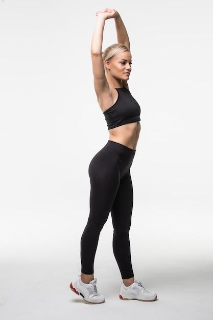 Uma linda e muito jovem loira está fazendo diferentes exercícios actobatic de alongamento de braços e pernas em branco Foto gratuita