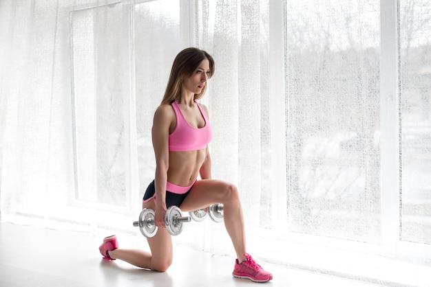 Uma linda garota atlética realiza exercícios nas nádegas em um fundo branco. ginástica Foto Premium