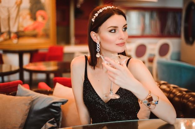 Uma linda garota bebe martini no lobby do hotel Foto Premium