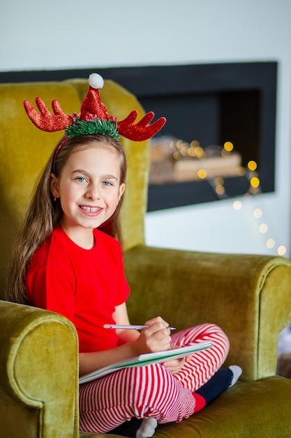 Uma linda garota com um chapéu de papai noel escreve uma carta para o papai noel perto da árvore de natal. infância feliz, um tempo para realizar desejos. Foto Premium