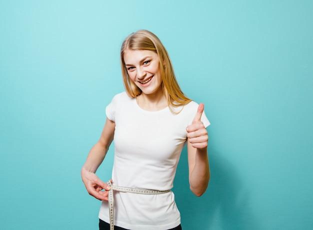 Uma linda garota loira que mede a cintura e está decepcionada com ela em um fundo azul Foto Premium