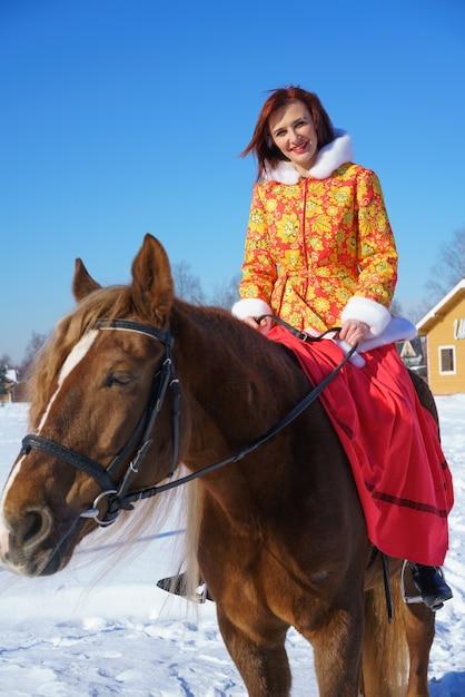 Uma linda jovem com uma jaqueta vermelho-amarela quente monta um cavalo em um dia gelado e ensolarado de inverno. pratica esportes equestres na temporada de inverno Foto gratuita