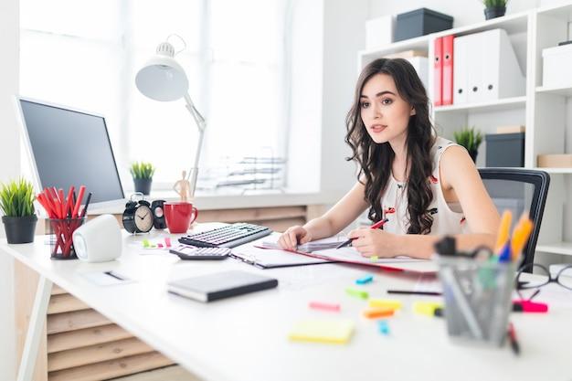 Uma linda jovem está sentado na mesa do escritório com documentos e uma caneta nas mãos dela e está negociando. Foto Premium