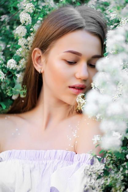 Uma linda jovem fica entre as árvores floridas. flores brancas. primavera. Foto Premium