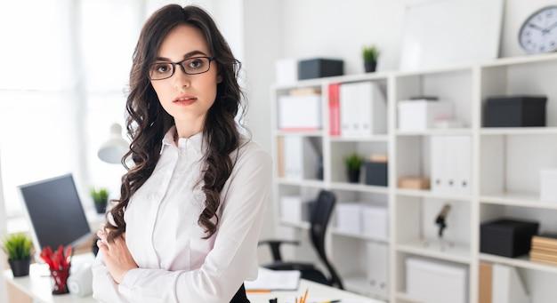 Uma linda jovem fica perto da mesa de escritório, as mãos entrelaçadas no peito Foto Premium