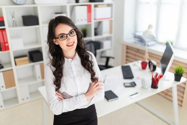 Uma linda jovem fica perto da mesa de escritório, mãos entrelaçadas no peito dela. Foto Premium