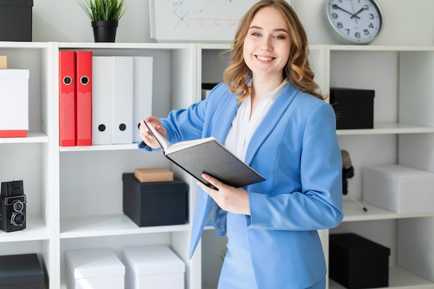 Uma linda jovem fica perto de um rack no escritório e detém um livro aberto nas mãos dela. Foto Premium