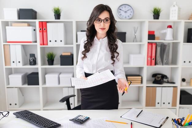 Uma linda jovem fica perto de uma mesa de escritório e detém uma caneta e um caderno nas mãos dela a menina está negociando Foto Premium