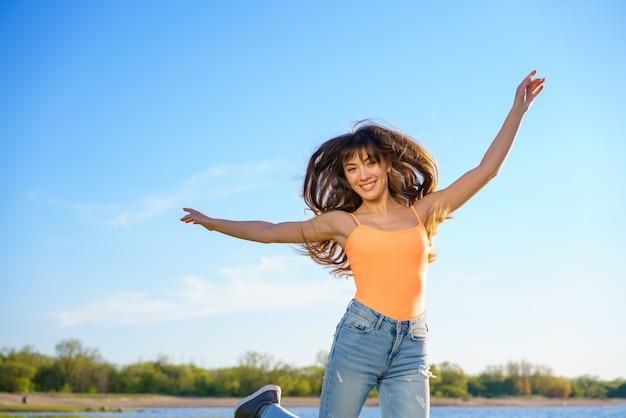 Uma linda jovem morena de jeans e camiseta laranja salta contra o céu em um dia ensolarado de verão Foto gratuita
