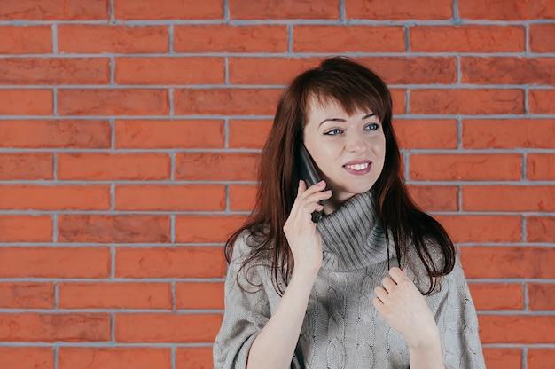 Uma linda jovem morena falando pelo celular, sorrindo feliz Foto Premium