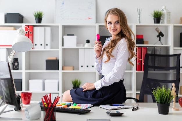 Uma linda jovem se sentou na mesa e segurava um marcador rosa na mão. antes da menina há documentos. Foto Premium