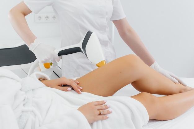 Uma linda jovem será submetida à depilação a laser com equipamentos modernos em um salão de spa. salão de beleza. cuidado do corpo. Foto Premium