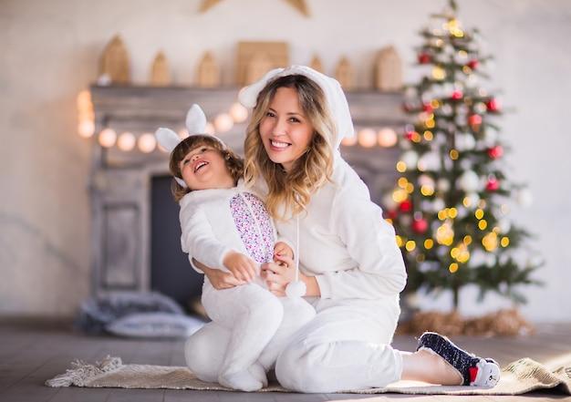 Uma linda mãe loira e uma criança em trajes de coelhinhos fofos brancos estão rindo no contexto de uma árvore de natal e uma lareira. foto de alta qualidade Foto Premium