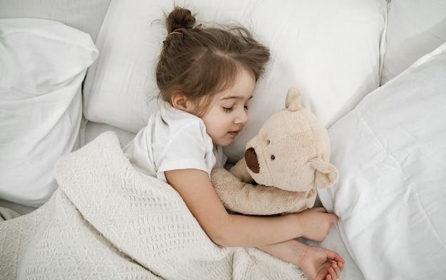 Uma linda menina está dormindo em uma cama com um ursinho de pelúcia. conceito de desenvolvimento infantil e sono. a vista do topo. Foto gratuita