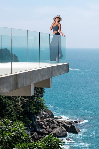 Uma linda morena com um corpo esbelto em um chapéu posa no terraço de vidro de seu hotel Foto Premium