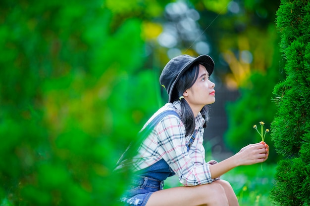 Uma linda mulher asiática usando um chapéu para relaxar e desfrutar no jardim verde como pano de fundo. Foto gratuita