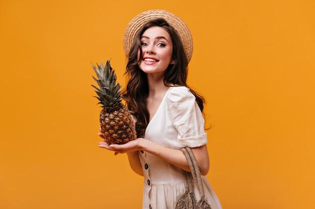 Uma linda mulher com vestido de algodão olha para a câmera com um sorriso e poses com abacaxi em fundo isolado. Foto gratuita