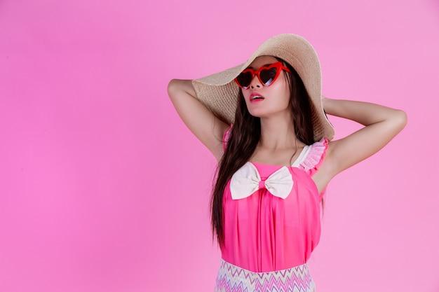 Uma linda mulher de óculos vermelhos com um grande chapéu em um rosa. Foto gratuita