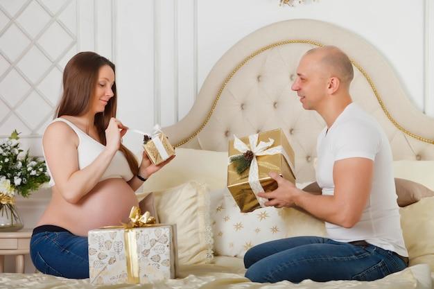 Uma linda mulher grávida e seu lindo marido trocam presentes de natal na cama no interior de seu quarto Foto Premium