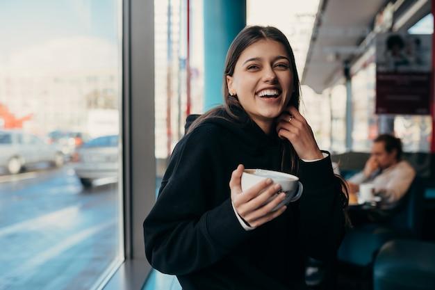 Uma linda mulher tomando café e sorrindo Foto gratuita