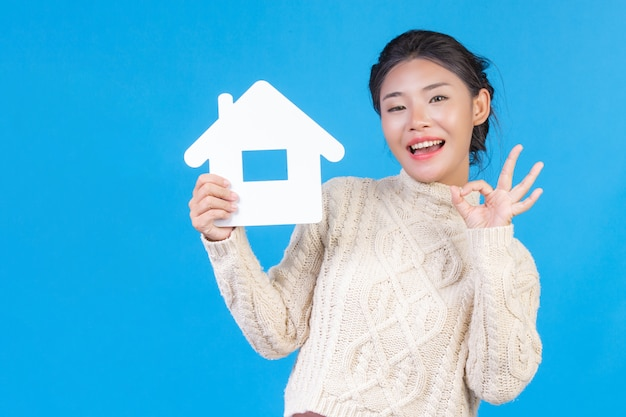 Uma linda mulher vestindo uma nova camisa branca de mangas compridas com um símbolo da casa. casa de negociação. Foto gratuita