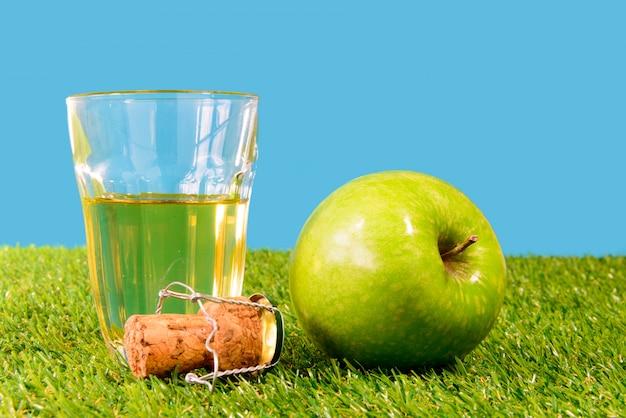 Uma maçã verde com um copo de cidra Foto Premium