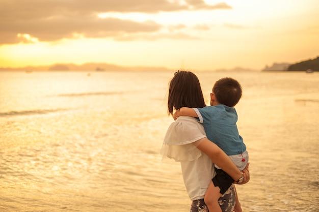 Uma mãe e filho ao ar livre ao pôr do sol com cópia espaço | Foto Grátis