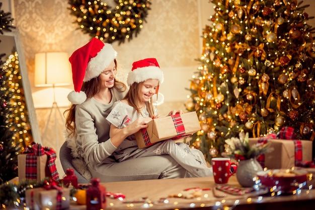 Uma mãe e uma família felizes embalam presentes de natal Foto Premium