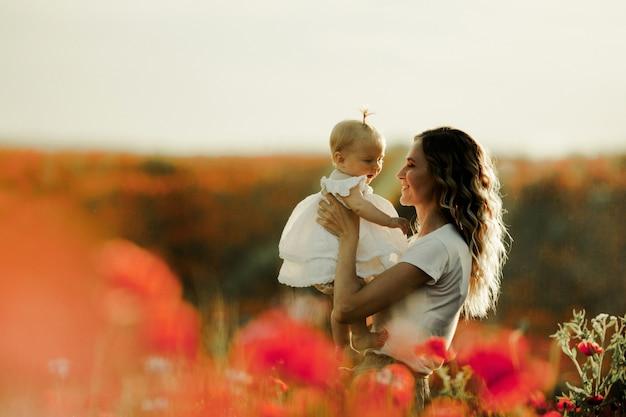 Uma mãe está segurando um bebê e sorri para ela Foto gratuita