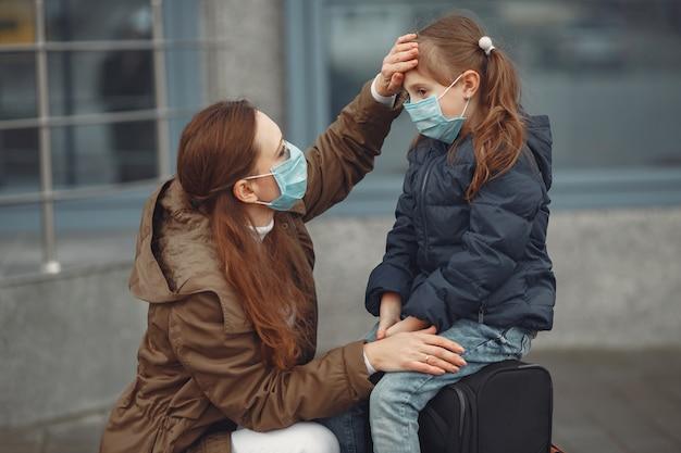 Uma mãe européia em um respirador com a filha está de pé perto de um prédio. a mãe está ensinando seu filho a usar máscara protetora para se salvar do vírus Foto gratuita