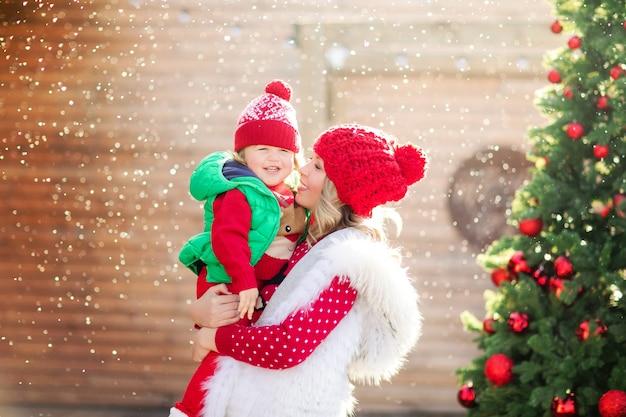Uma mãe loira segura seu filho risonho em um suéter de natal e um chapéu vermelho sob a neve no fundo de uma árvore de natal. foto de alta qualidade Foto Premium