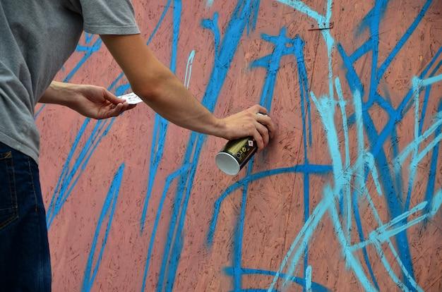 Uma mão com uma lata de spray que desenha um novo grafite na parede Foto Premium
