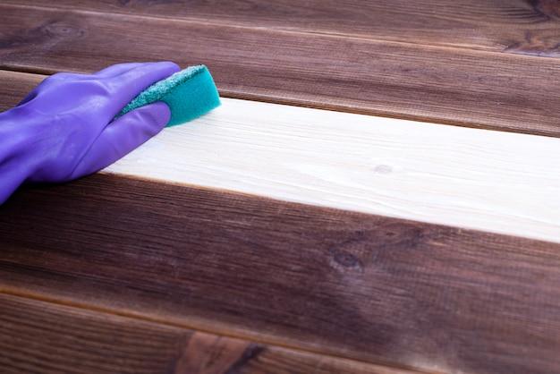 Uma mão em uma luva de borracha lava uma superfície de madeira. limpeza, limpeza do quarto. Foto Premium